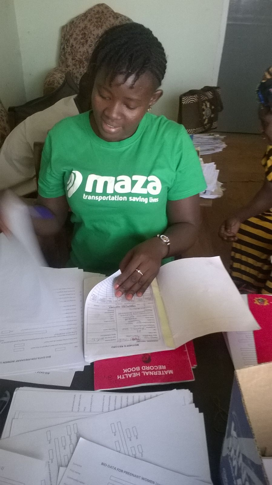 MAZA staff-Genevieve Nyewieh-screening ANC cards for pregnant women eligible for mobile phones
